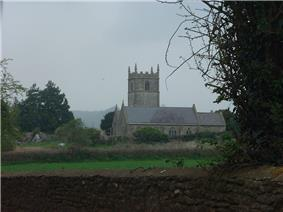 Gray stone building with square tower behind. In the foreground are green fields and bushes.