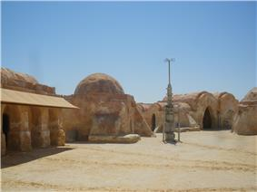 Rocky buildings and an antenna-like structure in a desert.