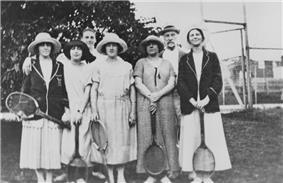 Five women standing with tennis rackets in hand
