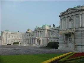 A large palace built of white stone in neo-baroque style. The facade is adorned with colons.