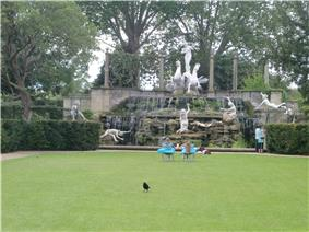 a grassy lawn in front of a statues complex several people sunbathe or sit in the midground facing in the background a group of white statues that are significantly larger than the people. In the foreground a black bird is walking away from the whole tableaux
