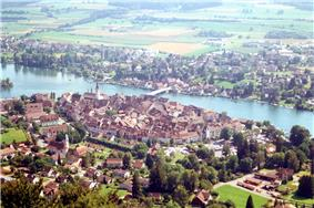 Aerial picture showing a small walled city dotted with red tile roofs and steeples; a wide river runs between it and another city. The farmlands on the far side are bathed in sunlight.