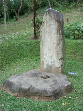 A tall, narrow standing stone set in a grassy area with an overgrown mound in the background. A flat circular stone lays at the base of the standing stone, it has been carved into a rough cogwheel shape.