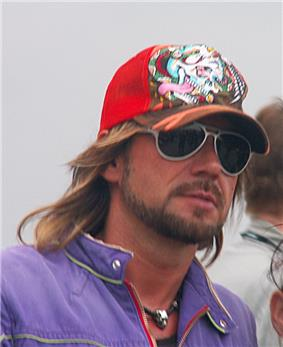Stephan Weidner—a bearded man with sunglasses, purple jacket and red baseball cap