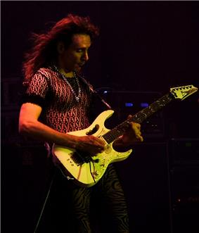 A man wearing black clothing and a chain necklace, holding an electric guitar
