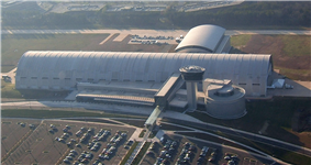 A large white building that resembles an airplane hangar. There is a large parking lot in the front with an enclosed glass bridge connecting it to the building.