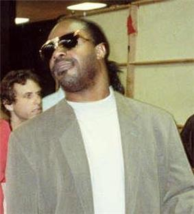 Stevie Wonder, a middle-aged African American man with his hair tied in a ponytail, dark sunglasses and stubble on his face. He wears a plain white tee-shirt and a grey jacket.