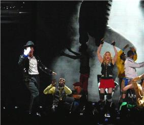 A group of males and a female performing on stage in front of a crowd of people. A male is shown blowing a kiss to the audience while wearing a white glove on his right hand and a white shirt with black pants and a jacket. An African American male wearing a white and dark grey shirt is shown in a crouched down position. The female is waving her hands in the air while wearing black fingerless gloves with a black shirt and pink shorts. There is also two other African American males in the background making hand gestures. Behind the people on the stage, there is a screen that shows a black and white photo.