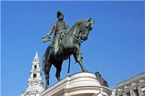 Photograph of a bronze statue with a man on horseback wearing a bicorn hat and military dress and who holds forth a scrolled sheaf of paper