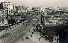 A large Japanese city with American soldiers patrolling the streets