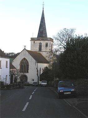 White painted church with square tower topped with a spire.