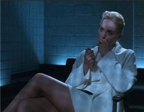 A blonde woman wearing a white jacket, top, and short skirt, her face half in shadow, sitting in an arm chair with her legs crossed. She holds a cigarette to her mouth with her right hand, and raises a lighter with her left. Behind her is dark furniture and the corner of the room, walled with white brick. From between the furniture and walls, unseen, floor-level lights cast a bluish glow over the scene.