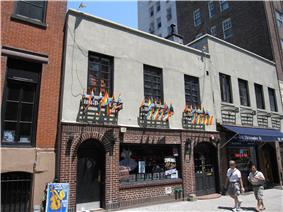 A two-story building with brick on the first floor, with two arched doorways, and gray stucco on the second floor off of which hang numerous rainbow flags.
