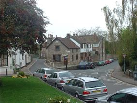 Street scene showing road junction and grey stone buildings with parked cars in front of them. To the left is a grassy area with a tree.
