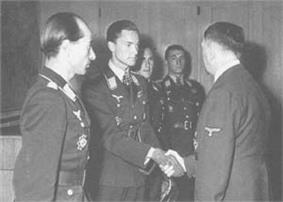 Four men all wearing military uniforms and decorations standing in row. The second man from the left is shaking hands with another man whose back is facing the camera.