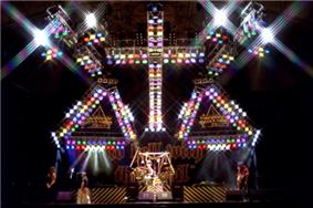 A color photograph of the band Stryper on stage under a large cross of lights