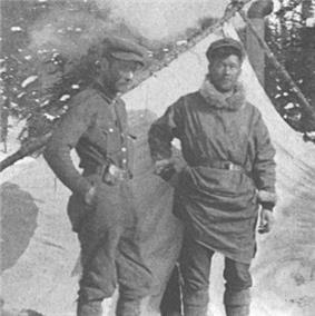 In a grayscale photograph, two men stand in front of a tent and snowy evergreen trees