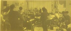 A somewhat indistinct photo on yellow paper of a crowded meeting room, showing student protesters with signs.  In the front, several well-dressed individuals appear to be gathering papers and departing.