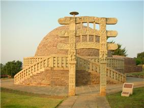 A heavily decorated gate in front of a stupa.