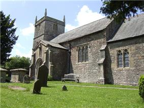 Gray stone building with square tower. Foreground is grass with gravestones.