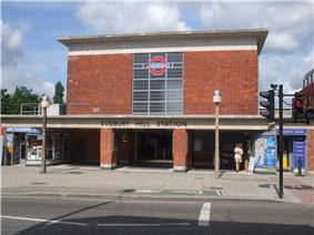 A red-bricked building with a rectangular, grey sign reading