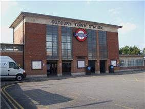 A red brick rectangular box shaped building with a concrete roof and two pairs of glazed screens