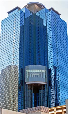 Ground-level view of a blue, glass high-rise; a circular pad sits atop the structure