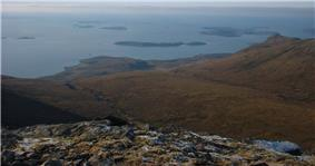 A view from a high rocky eminence with brown moorland below and a vista of small brown islands scattered in the sea beyond. A low bank of fog obscures the horizon.