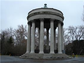 Open air round, marble structure resting on a layered base with twelve columns supporting the round, marble roof. There are leafless trees in the background.