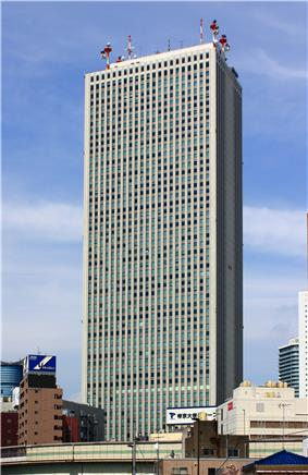 Ground-level view of a gray, rectangular high-rise lined with columns of windows