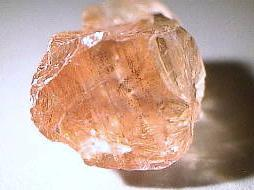 A multi-surfaced, pink rock with light reflecting at various points.