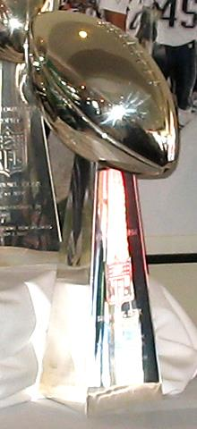 A silver trophy in the shape of an American football—an elliptical shape with pointed ends—standing on a pedestal of the same metal.