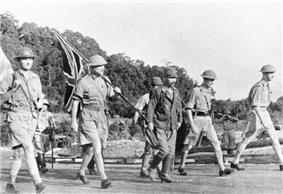 Four British soldiers in shorts and steel helmets, and three Japanese soldiers, one wearing a steel helmet. The British are carrying a Union Flag and a white flag.