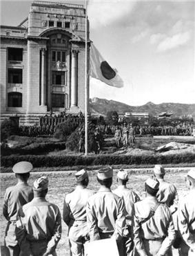 Men in military dress watch a flag being lowered.