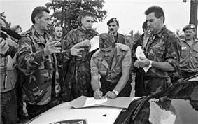 Colonel Bulat signing surrender on a police car bonnet while Lieutenant General Stipetić and Mr. Pajić observe.