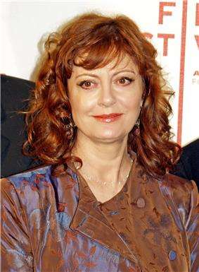 Upper torso of a red-haired female with a dark green shirt underneath a brown and blue jacket.