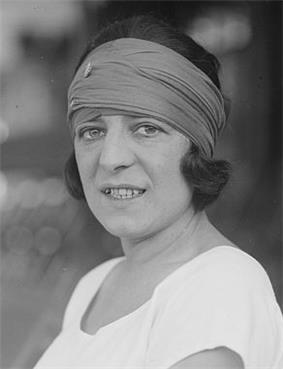 A woman looking at the camera with a colored bandanna on and a white shirt, which this picture is black and white