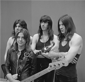 A black and white photograph of Quatro and her unnamed backing band. Quatro is holding her bass guitar, standing, and wearing a black leather jacket; her three taller and long-haired male bandmembers are standing behind her wearing dark tee shirts.