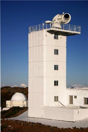 Photo of six-story building with fenced balcony containing large telescope