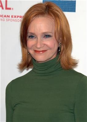 A color photograph of Swoosie Kurtz, a woman with blue eyes and brown-red hair, in a green sweater