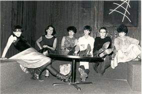 Six dark haired women sitting at a table in a black room