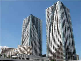 Ground-level view of two similar rectangular high-rises; each building is painted to have curved sections of color on the primarily white facades