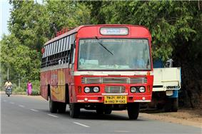 A bus in a road with tress in the background
