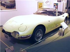 A roadster with headlights retracted and a smooth, moulded design.