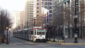 A light-rail train surrounded by tall buildings