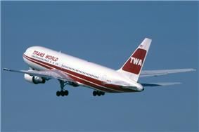 TWA jetliner in red and white livery during takeoff, with landing gears still down.