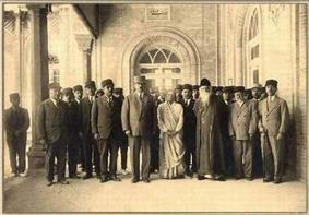 Group shot of dozens of people assembled at the entrance of an imposing building; two columns in view. All subjects face the camera. All but two are dressed in lounge suits: a woman at front-center wears light-coloured Persian garb; the man to her left, first row, wears a white beard and dark-coloured oriental cap and robes.