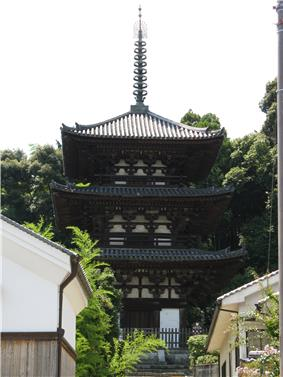 Wooden three-storied pagoda with white walls and dark beams.