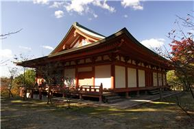 Wooden building with white walls, vermillion red beams, slightly raised floor and a hip-and-gable roof.