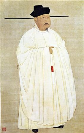 A short man in heavy white robes, wearing a black hat with long horizontal protrusions coming from the bottom of the hat. The man has a small, pointed beard and a small mustache.